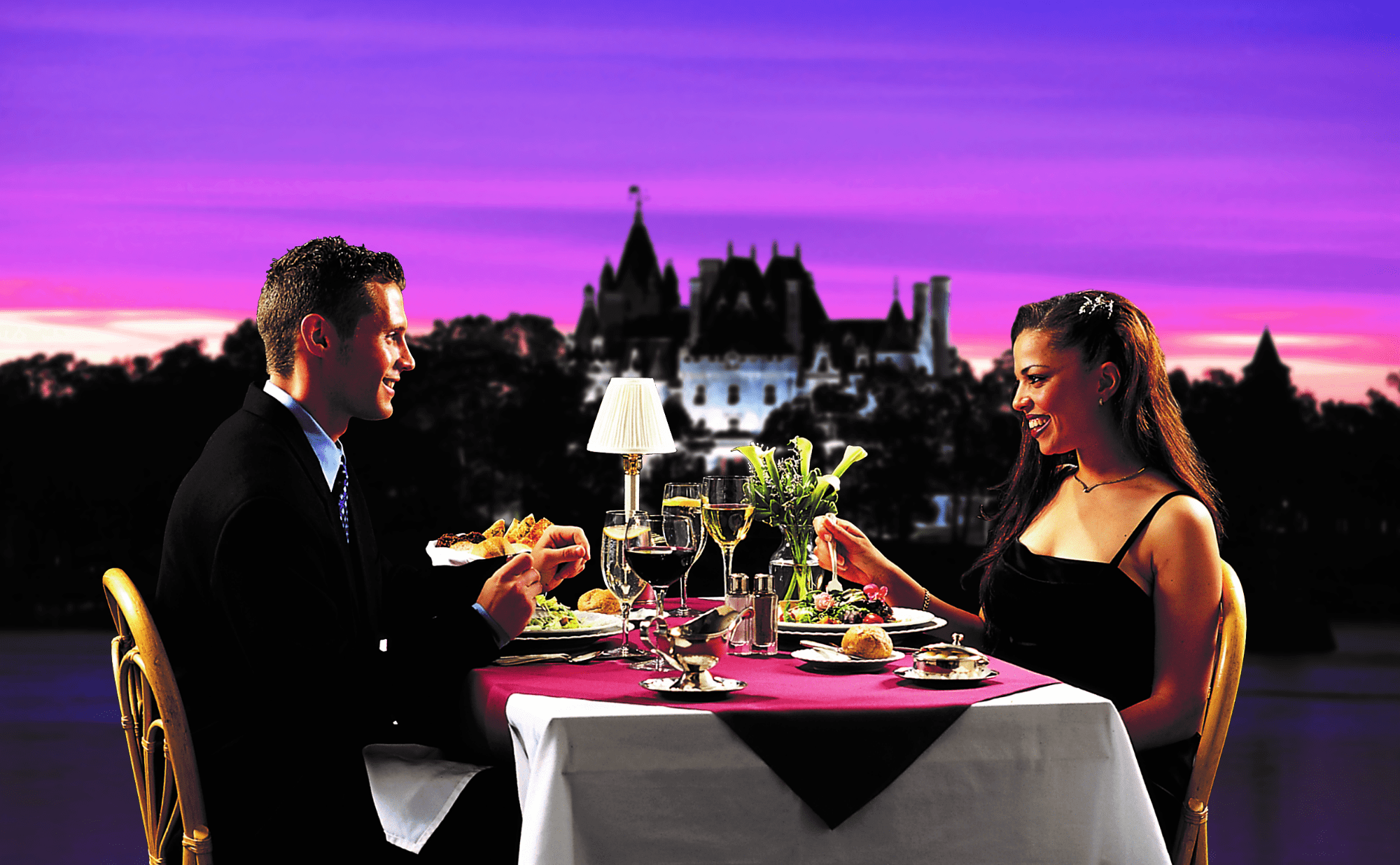 A couple enjoys a sunset dinner in front of a castle at riveredge resort
